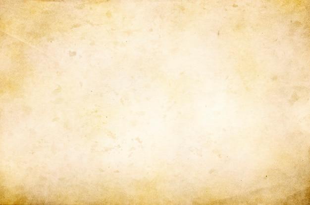 Un vecchio sfondo grunge con una trama di carta ruvida con macchie e striature e una copia dello spazio