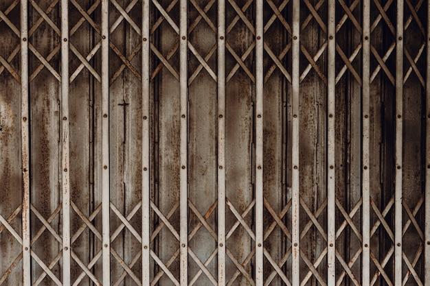 Vecchia porta a soffietto con persiana arrugginita del grunge per negozio chiuso o business down concept, pattern texture o cancello in acciaio.