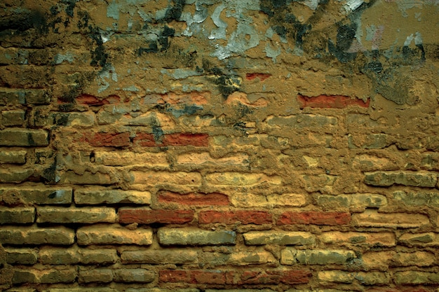 Vecchio grunge weathered texture muro di mattoni con intonaco mancante e graffiti verniciati a spruzzo