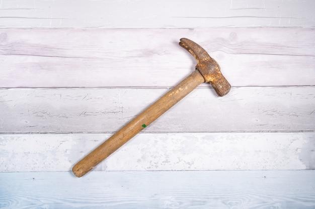 Il vecchio martello strappa i chiodi delle casseforme su uno sfondo di vecchie assi