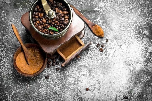 Vecchia smerigliatrice a mano con chicchi di caffè. su fondo rustico.