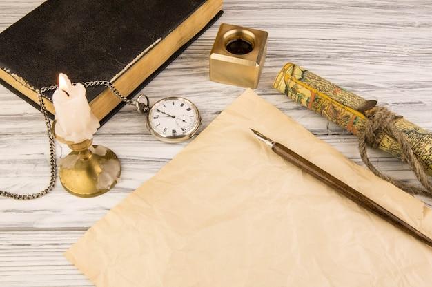Il vecchio manico in piuma e un foglio di carta con una candela