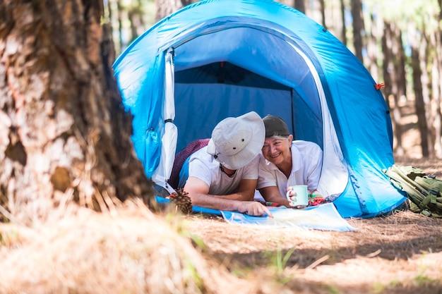 Vecchia coppia caucasica allegra felice insieme all'interno di una tenda che guarda una mappa e sceglie le prossime destinazioni