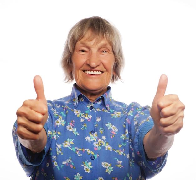 Vecchia donna felice che mostra segno ok su uno sfondo bianco