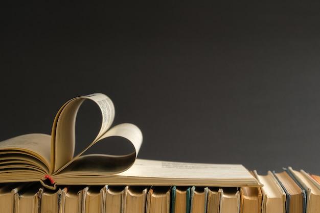 Vecchia pagina del libro con copertina rigida decorata a forma di cuore per amore nel giorno di san valentino.