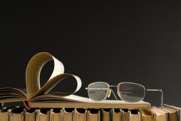 Vecchia pagina di libro con copertina rigida decorata a forma di cuore con occhiali sul lato per amore il giorno di san valentino