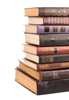 Vecchi libri della pila con copertina rigida isolati su bianco