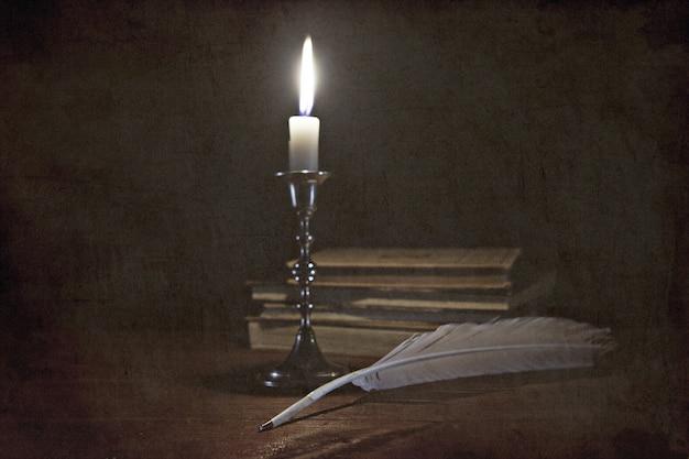 Vecchia storia natura morta con candela e libri su sfondo grunge
