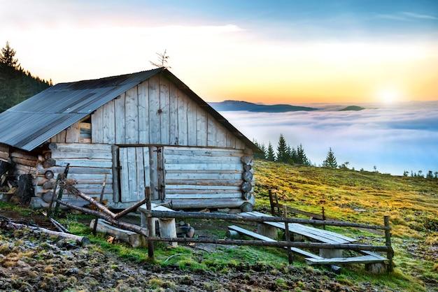 Vecchia casa di fronte a una natura bellissima con nuvole oceano, campo di erba e montagne