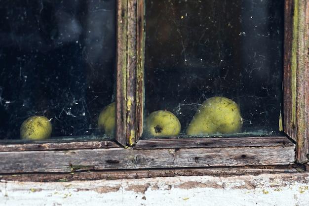 Vecchia casa finestra cornice in legno e pere dietro il vetro con ragnatela, luogo abbandonato