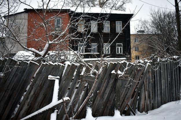 Vecchia casa e staccionata in legno in inverno