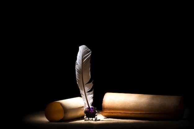 Vecchio calamaio con piuma vicino a pergamene contro il nero.