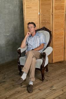 Un vecchio uomo intelligente che si riposa su una poltrona