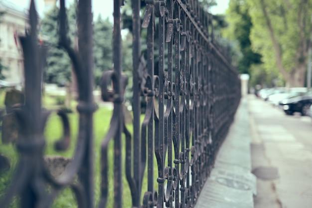 Vecchia recinzione in ferro nel parco cittadino, primo piano.