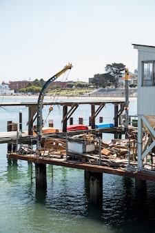 Vecchio molo pieno di utensili da pesca vicino a un porto