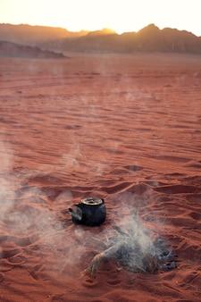 Il vecchio bollitore sta bollendo all'aria aperta in un deserto di sabbia beduina wadi rum in giordania