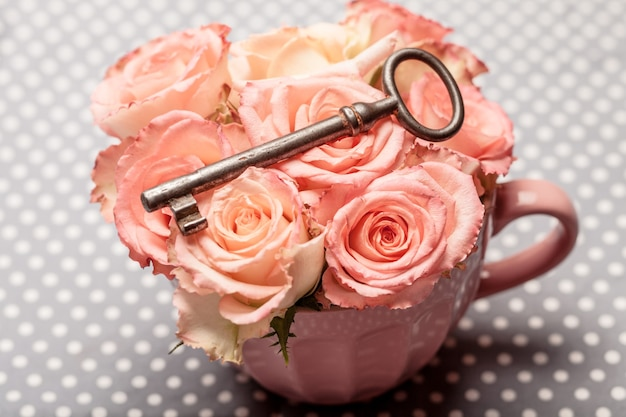Vecchia chiave su rose rosa in una tazza. arredamento vintage
