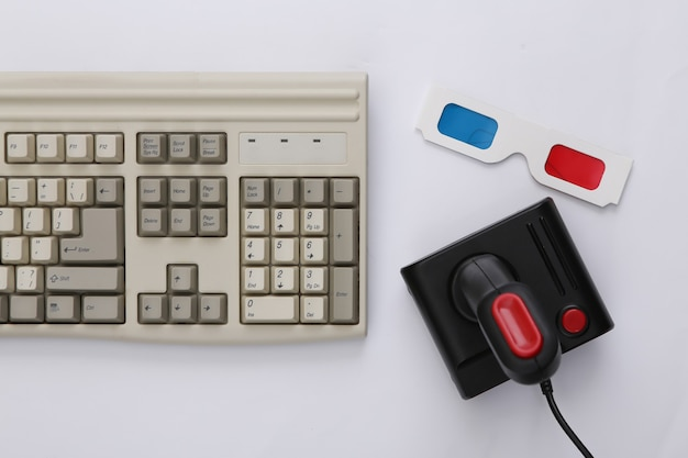 Vecchia tastiera, occhiali 3d e joystick su sfondo bianco. gioco retrò. videogioco stereo. anni 80. vista dall'alto. lay piatto