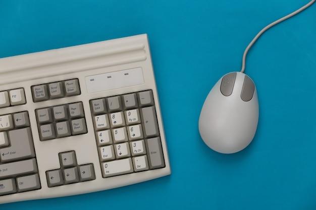 Vecchia tastiera e mouse per pc su sfondo blu. vista dall'alto. lay piatto