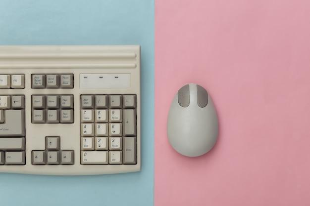 Vecchia tastiera e mouse per pc su sfondo rosa blu. vista dall'alto. lay piatto