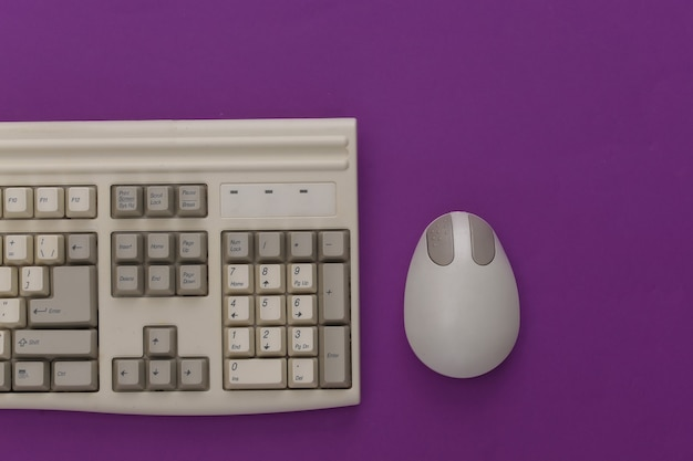 Vecchia tastiera e mouse per pc su sfondo viola. vista dall'alto. lay piatto
