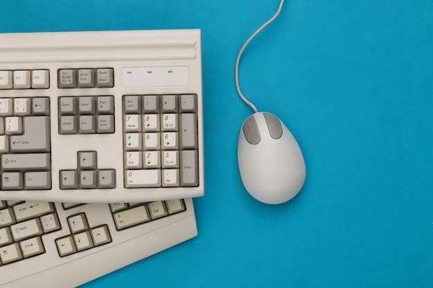 Vecchie tastiere e mouse per pc su sfondo blu. vista dall'alto. lay piatto