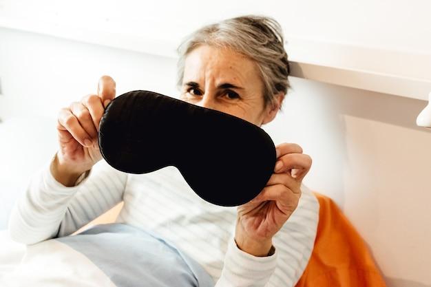 Una vecchia signora che mostra una maschera per dormire mentre sorride in una moderna camera da letto
