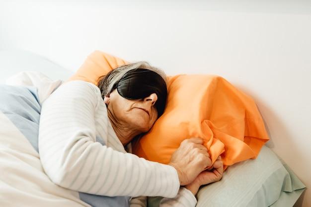 Una vecchia signora che dorme usando una maschera per il viso in una moderna camera da letto