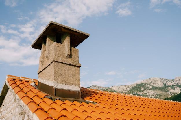 Un vecchio grande camino su un tetto arancione sullo sfondo di montagne e cielo