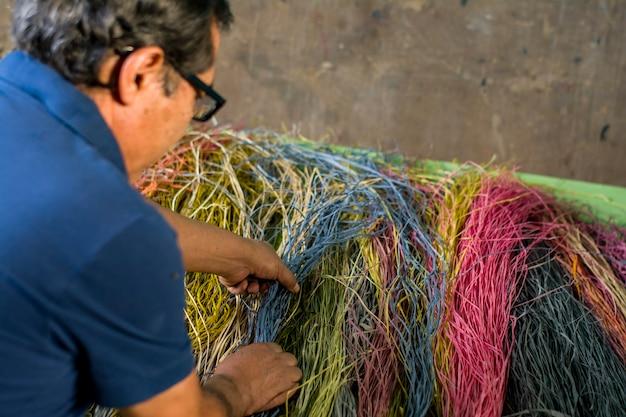 Vecchio artigiano latinoamericano che tesse con le sue mani mostrando i suoi strumenti e materiali