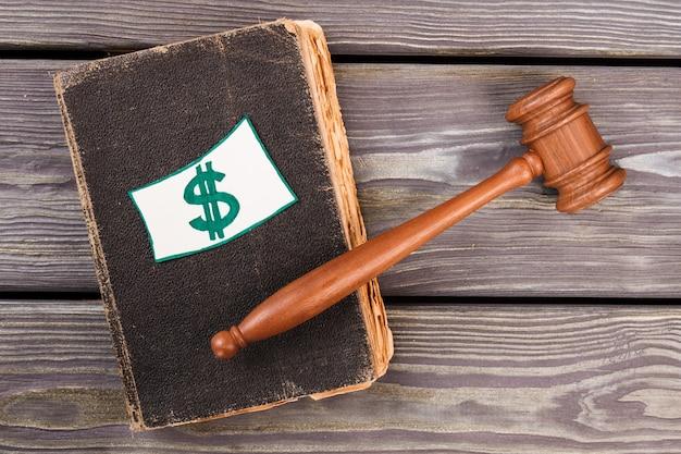 Vecchio libro di legge con il segno del dollaro. martelletto del giudice in legno marrone.