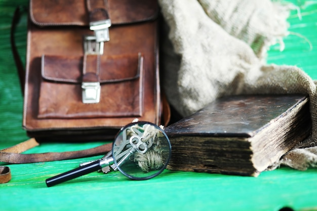 Vecchia borsa in pelle con una lente di ingrandimento su uno sfondo di tavolo in legno marrone viaggiatore con spazio per le copie.