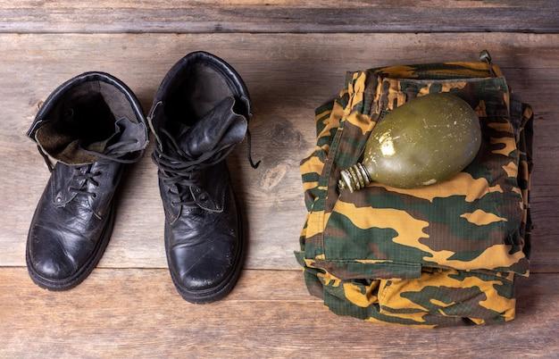 Vecchi stivali dell'esercito degli uomini di cuoio neri, uniforme militare e boccetta dell'acqua sulla vista superiore del primo piano di legno del fondo