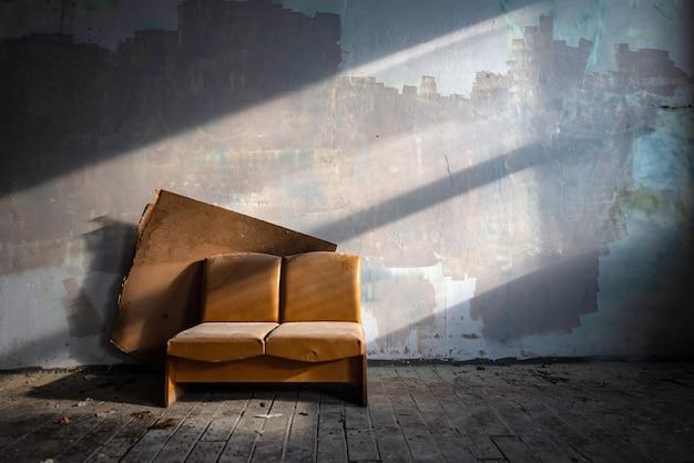 Vecchio divano in pelle in fabbrica abbandonata lato edificio illuminato dal sole.