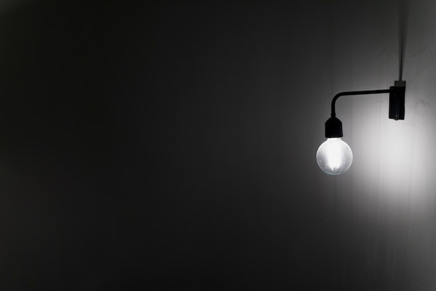 Una vecchia lampadina sul muro di cemento nel buio