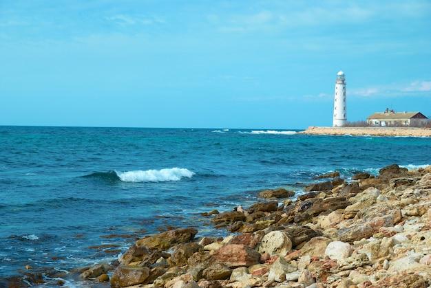 Vecchio faro sulla costa del mare. tempesta, onde e cielo blu.