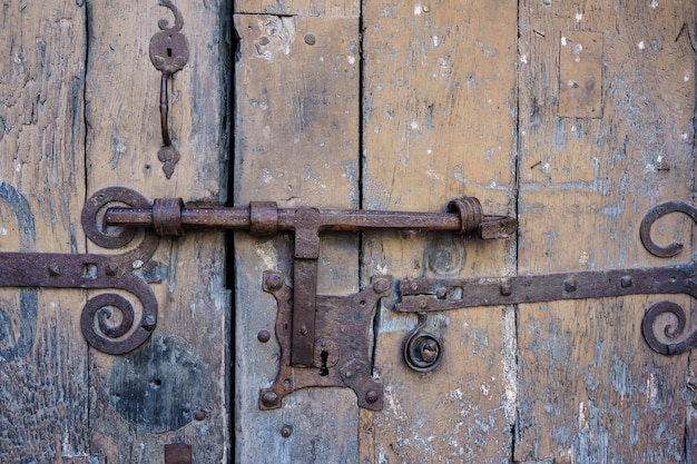 Una vecchia serratura di una porta arrugginita e con il vecchio legno
