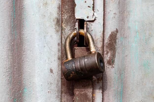 Vecchio cancello di ferro bloccato con lucchetto in acciaio, primo piano.
