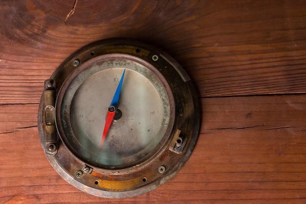 Vecchia bussola magnetica di navi in ottone antico montata su un armadio in legno per la navigazione del globo durante una crociera o un viaggio, con copyspace