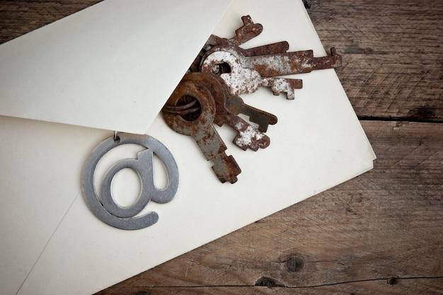 Vecchia busta postale e firmare l'e-mail su uno sfondo di legno