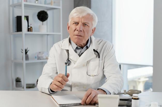Vecchio medico maschio nel suo ufficio