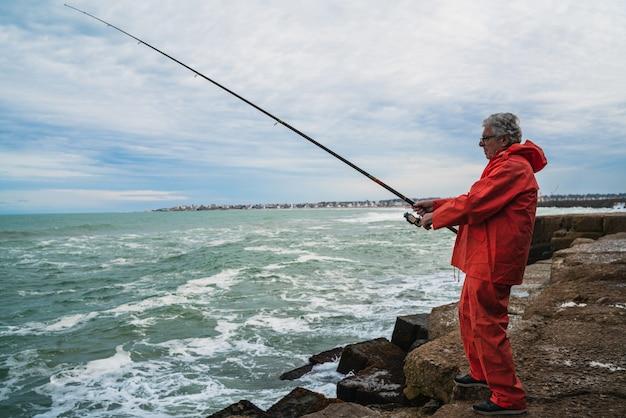 Uomo anziano che pesca in mare.