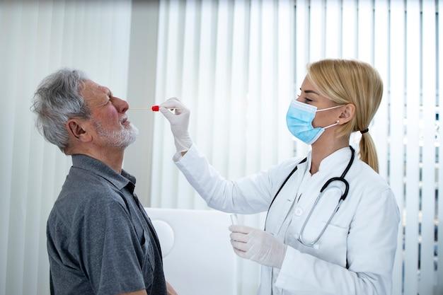 Uomo anziano che riceve il test pcr presso l'ufficio dei medici durante l'epidemia di covic19