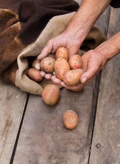 Mano di uomo anziano con patate fresche raccolte con terreno ancora sulla pelle, fuoriuscita da un sacchetto di tela da imballaggio, su una tavolozza di legno grezzo.