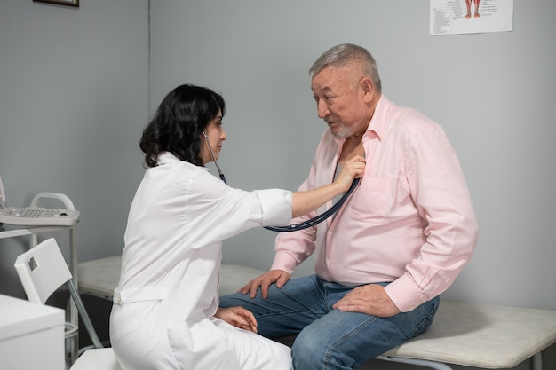 Un vecchio che si fa controllare il battito cardiaco dal medico con uno stetoscopio.