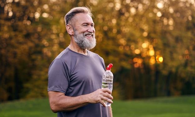 Il vecchio con in mano una bottiglia d'acqua