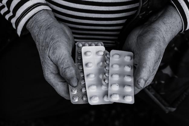 Vecchio che tiene in mano delle pillole