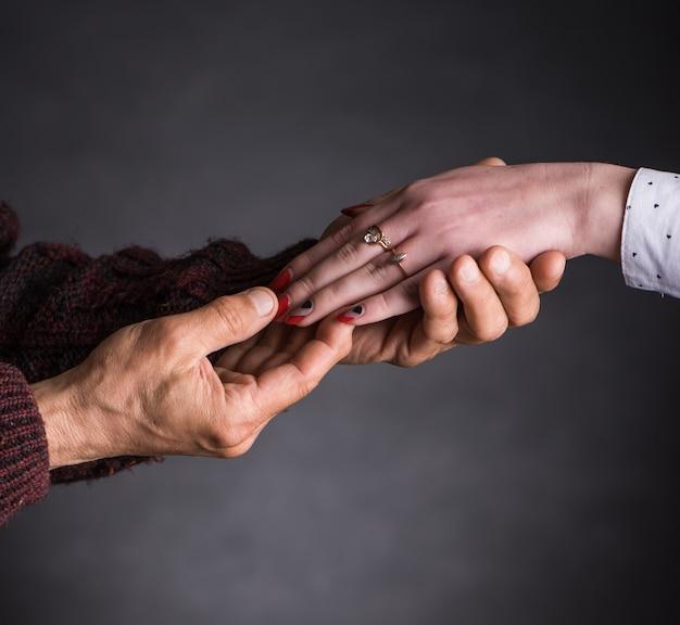 Vecchio che tiene la mano di una giovane donna su uno sfondo grigio