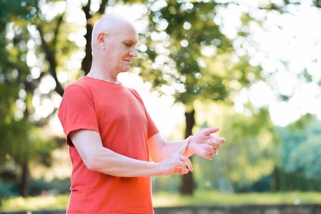 Uomo anziano che misura il polso della frequenza cardiaca sul polso