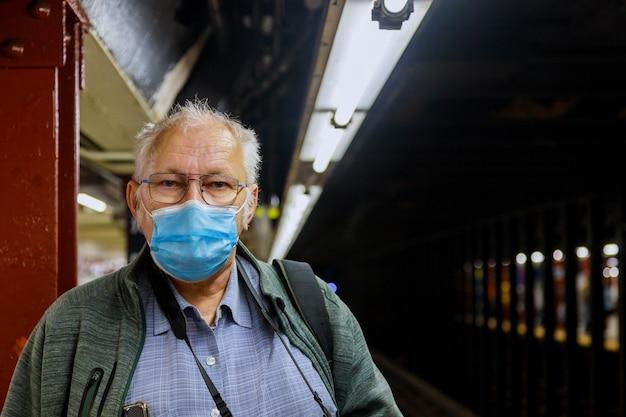 Un vecchio in maschera medica in piedi nell'epidemia di coronavirus della metropolitana in attesa della metropolitana